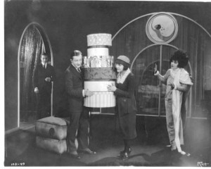 "1921: Alla Nazimova with hatboxes and Rudolph Valentino in ""Camille"""