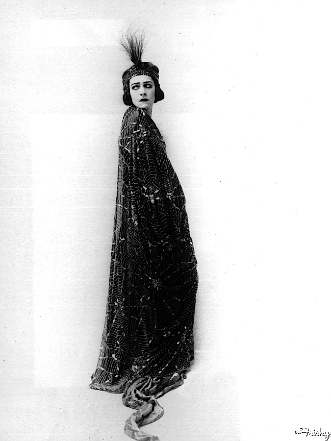 Circa 1915: Promotional studio portrait of Alla Nazimova wearing a robe with a spider web motif.