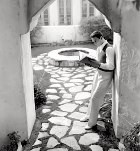 Man reading on a side path of the Garden of Allah Hotel