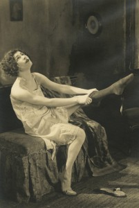 "1921: Alla Nazimova putting on her stocking in ""Camille"""